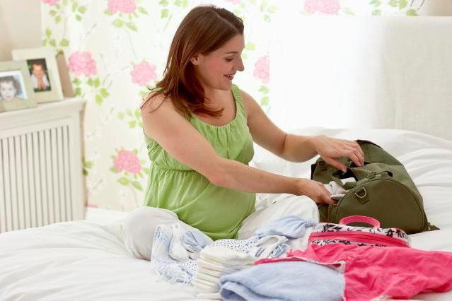 Pregnant woman sitting on bed packing hospital bag (labour bag) with nappies and clothes