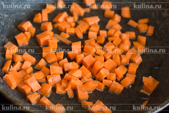 В сковороде разогреть растительное масло. Морковь нарезать кубиком, выложить в сковороду и слегка обжарить.