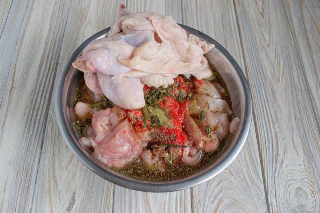 Куриное мясо и кожу кладём в глубокую миску, добавляем маринад и оставляем на 1 час